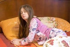 Bostezo soñoliento del niño en cama Niña soñolienta en la cama foto de archivo libre de regalías
