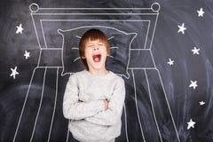 Bostezos del muchacho y en el fondo de la cama pintada Foto de archivo libre de regalías