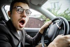 Bostezos jovenes del individuo mientras que mira la cámara Él se está sentando en su coche Sus manos están en el volante fotografía de archivo