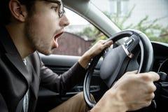 Bostezos jovenes del individuo mientras que se sienta en su coche Sus manos están en el volante fotografía de archivo libre de regalías