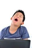 bostezos muchacho en blanco mientras que usa el ordenador portátil foto de archivo