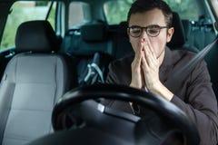 Bostezos soñolientos del hombre joven mientras que cubre su boca con ambas manos Concepto de la seguridad en carretera imagenes de archivo