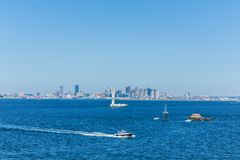 Boston City Skyline from Distance. Boats in Early Morning Boaton Harbor royalty free stock photography