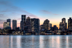 Boston city skyline at dusk. The Boston skyline at dusk with the water from the harbor int he foreground Royalty Free Stock Photo