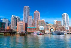 Boston cityscape reflected in water, skyscrapers and office buildings in downtown. View from Boston harbor, Massachusetts, USA Royalty Free Stock Image