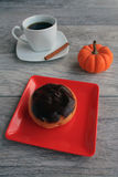 Boston Cream dough nut with mug of pumpkin spice coffee Stock Photo