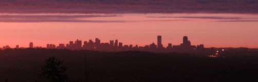 Boston dawn skyline. Massachusetts USA city sky line at dawn with purple and red clouds ominous over the new england city royalty free stock photos