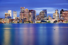 Boston Downtown Skyline at Blue Hour. Boston downtown taken from Jeffies Point in a fantastic cloudy evening, with skyscrapers lights reflected in the bay water Royalty Free Stock Photo