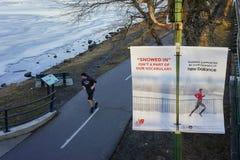 Runner running along Charles River Royalty Free Stock Image