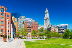 Boston - June 2016, USA: View of The Custom House Tower, surrounding buildings in downtown and park with trees, lawn and benches Stock Photography