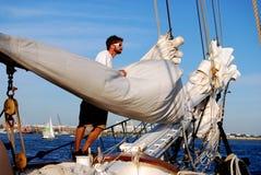 Boston, MA: Sailor Tending Sails. BOSTON, MASSACHUSETTS: Sailor tends to sails on the Liberty Clipper sailing ship stock photography