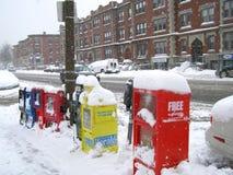 Boston, MA/USA- 22 de janeiro de 2014: Distribuidores do jornal e do compartimento/caixas sob a neve em um dia nevado foto de stock