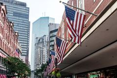Boston, MA USA Shopping Mall Store front with american flags waving with skyscrapers in the background skyline. Boston, MA USA - Shopping Mall Store front with Royalty Free Stock Photos