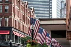 Boston, MA USA Shopping Mall Store front with american flags waving with skyscrapers in the background skyline. Boston, MA USA - Shopping Mall Store front with Royalty Free Stock Image