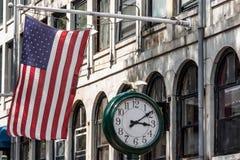 Boston, MA usa - zakupy centrum handlowego sklepu przód z flaga amerykańskiej falowaniem z dużym zegarem obok go Fotografia Stock