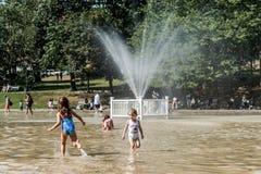 Boston MOR, USA 06 09 2017 - Det familjbarn och folket tycker om att kyla sprej på grodadammet på varma den offentliga sommardage Arkivfoto
