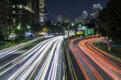 Only in Boston at night. Boston, Massachusetts skyline at night, featuring car lights trails on the foreground and illuminated buildings on the background royalty free stock photos
