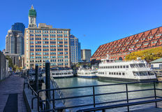 BOSTON - OCTOBER 2015: City port and buildings on a sunny day. B. Oston attracts 10 million people annually Stock Photos