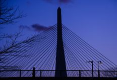 A Boston pedestrian at dusk with the Zakim Bridge looming in the background. royalty free stock photo