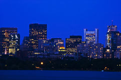 Boston's Financial Distric in the Evening. A view of Boston across the Charles River with a light trail from an air plane in the sky Stock Images