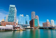 Boston skyline. Boston - June 2016, MA, USA: Boston skyline, old historic ship in Tea Party museum and modern buildings in downtown reflected in the water of stock photography