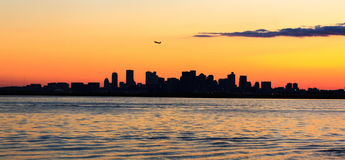 Boston Skyline at sunset with plane taking off Stock Photography