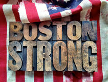 Boston Strong words on flag. The words 'Boston Strong' in letterpress wood type on a torn and bloodied American flag royalty free stock photos