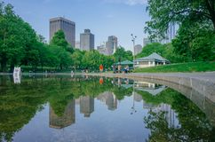 Frog Pond in Boston Common with reflection of buildings and locals walkings and resting by the water stock photo