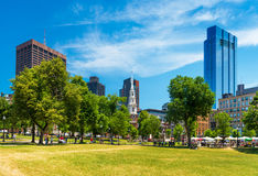 Boston, USA: People sitting on grass and walking around in Boston Common Park, view on Skyscrapers and Park street Church Royalty Free Stock Photos