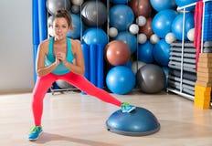 Bosu在健身房锻炼的一腿矮小女孩锻炼 免版税库存照片