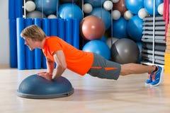 Bosu金刚石增加白肤金发的人健身房锻炼 免版税库存照片