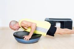 Bosu core exercise. Elderly man making bosu core exercise stock images