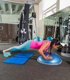 Bosu empuja hacia arriba a la mujer del pectoral en el entrenamiento del gimnasio Fotografía de archivo