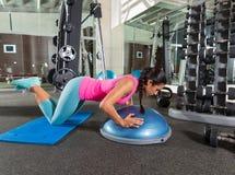 Bosu knä skjuter upp liggande armhävningkvinnan på idrottshallen Royaltyfri Foto