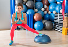 Bosu one leg squat girl exercise at gym workout. And swiss ball background Royalty Free Stock Photos