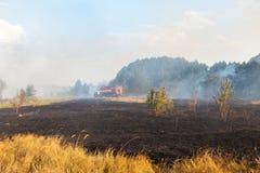Boswildfire toe te schrijven aan droog winderig weer Brandmotor met brandbestrijders die vlam, Blauwe die hemel behandelen met zw stock fotografie