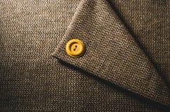 Botão amarelo em uma matéria têxtil marrom dobrada Foto de Stock Royalty Free