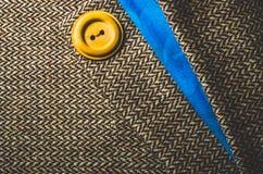 Botão amarelo na tela marrom e azul dobrada Fotografia de Stock