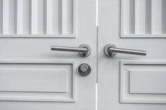 Botão de porta de aço inoxidável na porta branca imagens de stock royalty free
