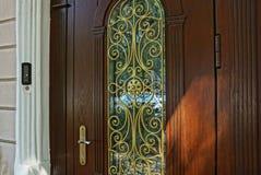 Botão de porta amarelo em uma porta marrom com um teste padrão foto de stock