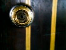 Botão de porta de bronze do metal na porta de madeira imagens de stock royalty free