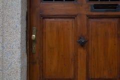 Botão de porta de bronze em uma porta de madeira velha fotos de stock royalty free
