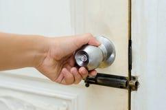 Botão de porta da porta de madeira da porta do botão ou punho inoxidável branco, mão imagens de stock