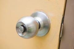 Botão de porta de aço na porta amarela imagens de stock