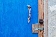 Botão de porta do ramo de árvore na porta azul, fotografia de stock