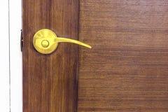Botão de porta dourado na porta de madeira fotografia de stock