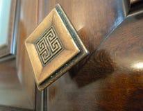 Botão de porta inoxidável da porta de madeira ou botão na porta de madeira na iluminação bonita fotografia de stock