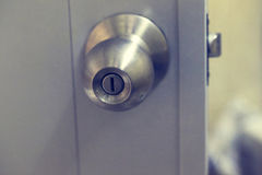 Botão de porta inoxidável na porta branca Foto de Stock