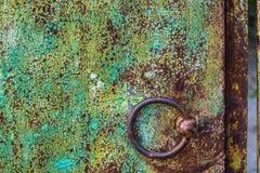 Botão de porta marrom do ferro redondo na parede gasto verde imagens de stock royalty free