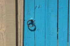 Botão de porta nas placas de uma porta de madeira azul e de uma cerca cinzenta imagem de stock royalty free